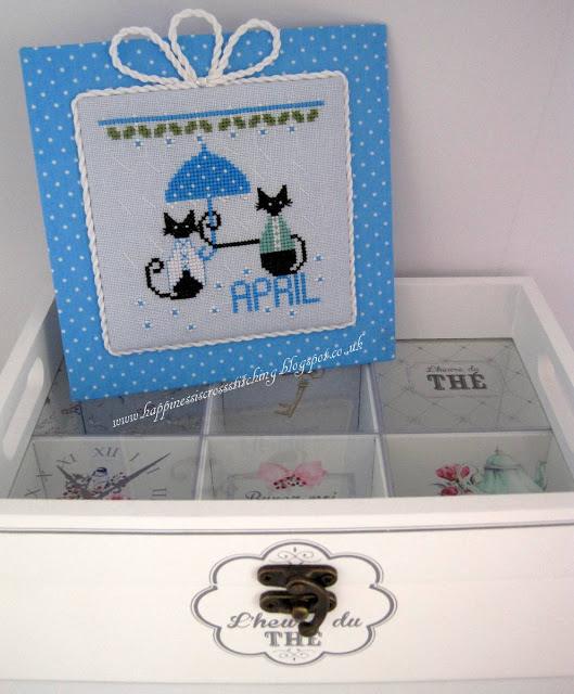 April cat cross stitch design featuring a small black mini cat holding an umbrella over Miss Mini Cats head to keep her dry from the rain.