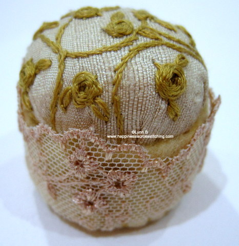 Embroidered silk bottle cap pincushion finished with roses and vines using gold coloured threads