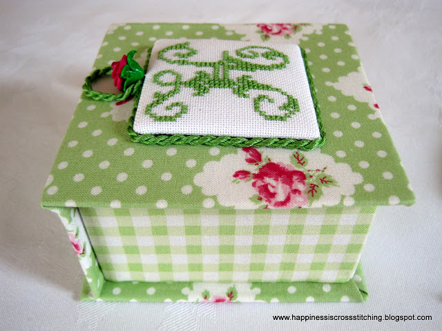 Cross stitch covered box decorated with green fabric and pink roses in the design