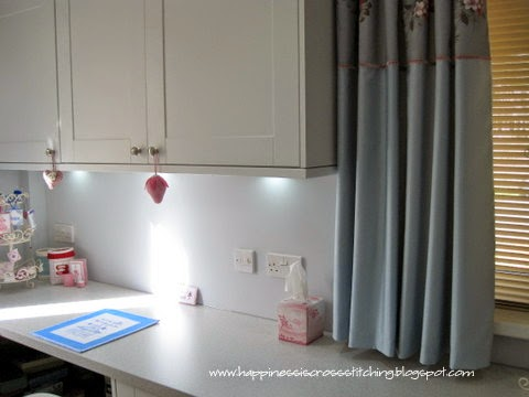 My craft room includes lots of cupboard space for my cross stitching and crafting, white cupboards and pale grey work surfaces compliment each other. The gorgeous pale blue curtains feature a soft grey rose panel of flowers along the top.