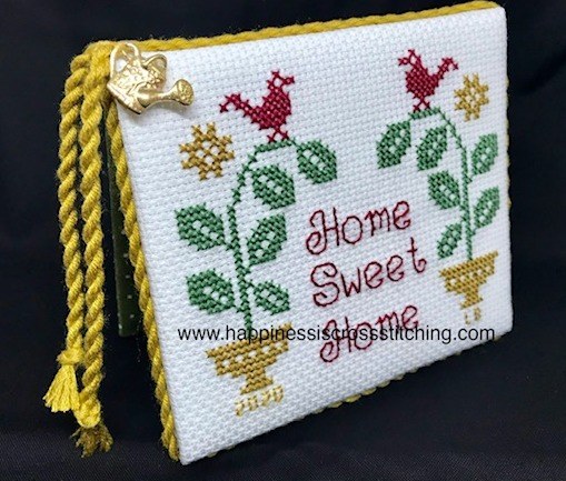 Cross stitched flatfold with the words Home Sweet Home and stay safe stitched on the front in red letters. A red bird sits on a green plant pot.
