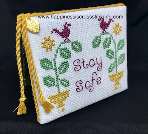 Cross stitched flatfold with the words stay safe stitched on the front in red letters. A red bird sits on a green plant pot.
