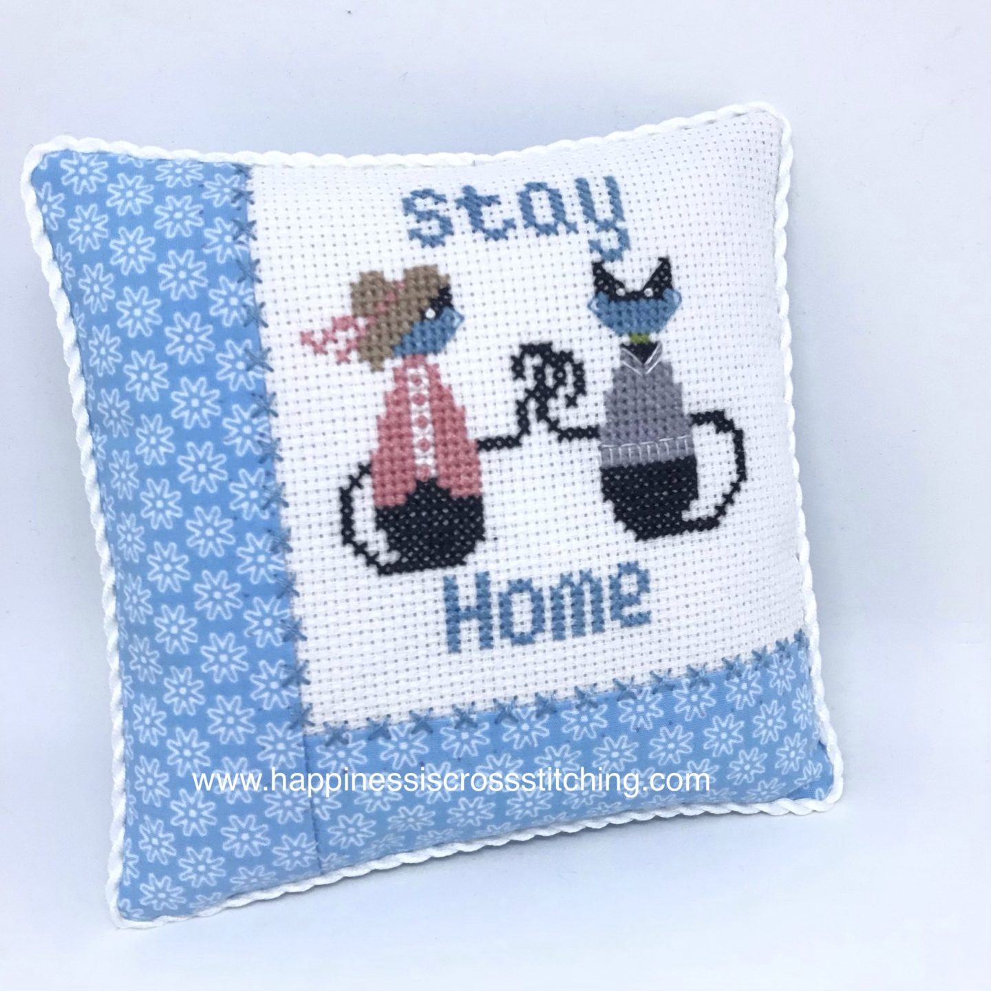 Cross stitched pillow featuring black mini cats crossed stitched onto white aida fabric. Miss mini cat is wearing a pink top and a pretty straw hat and Mr Mini Cat is wearing a grey jumper, they are both wearing blue facemaskes to protect them from the virus.