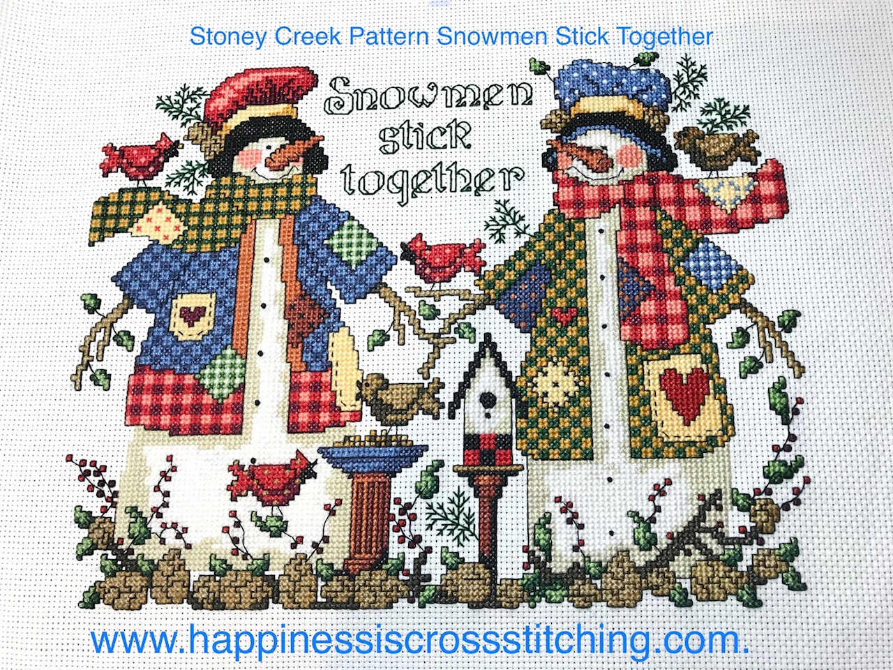 Completed cross stitch of two snowmen dressed in brightly coloured clothes  out in the snow.