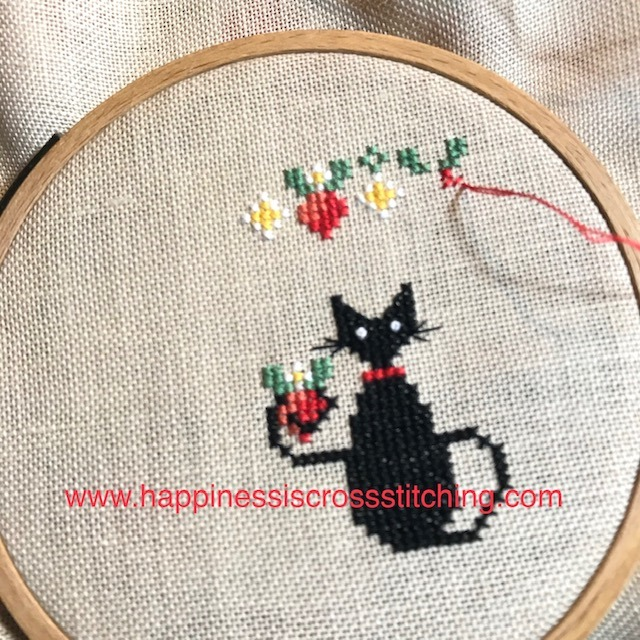 A cross  stitch pattern featuring a small black cat holding a srawberry in her tail, there is a bowl of strawberries on the table and a garland of strawberries above the cats head.