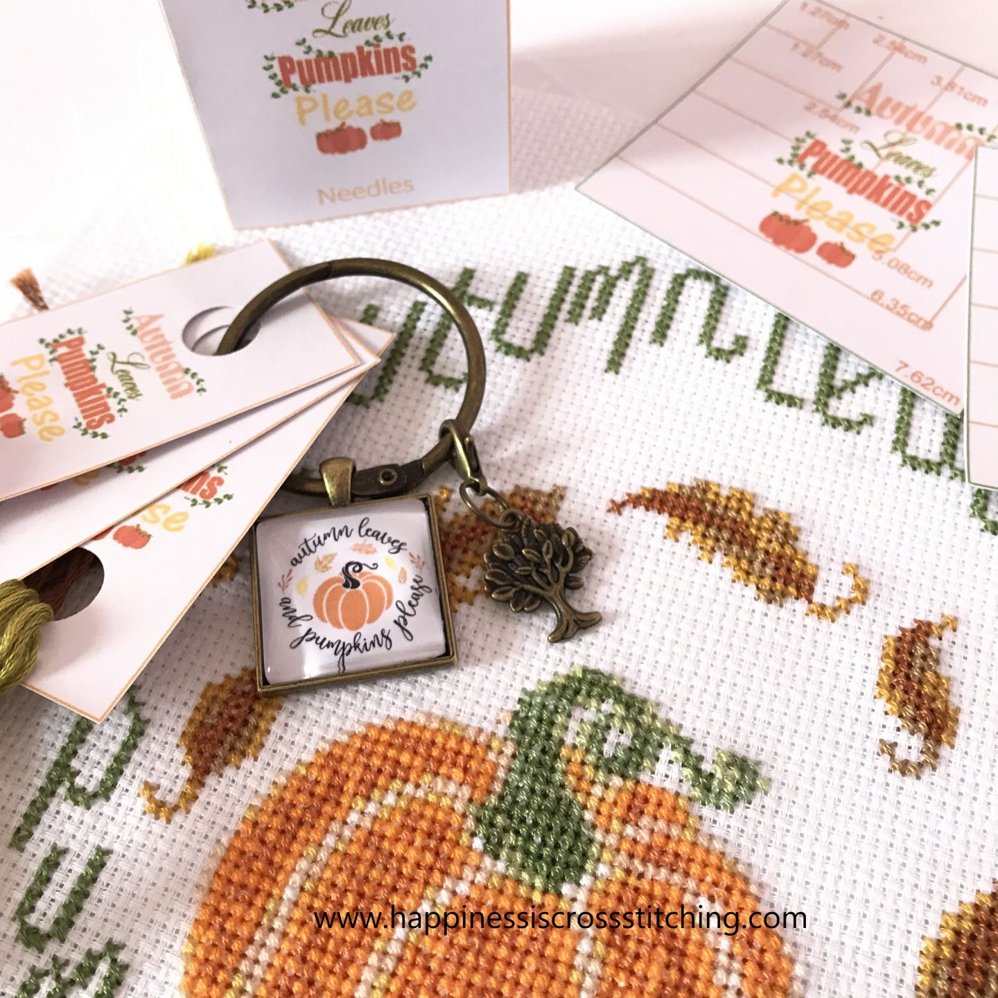 Autumn cross stitch pattern with pumpkin and leaves.