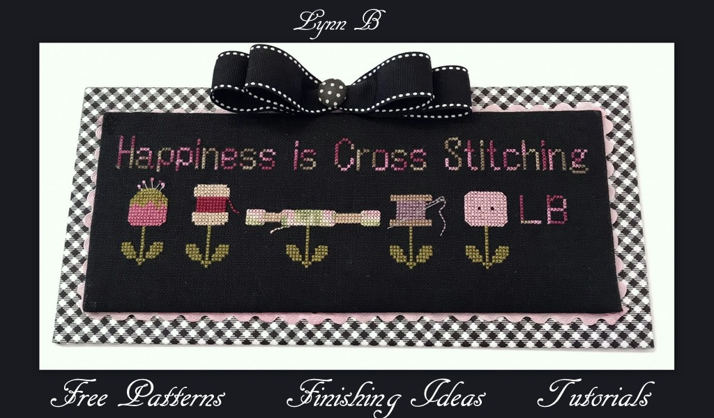 Happiness is cross stitching pattern featuring a needle, thread and skeins of thread on the top of a stem with two leaves.