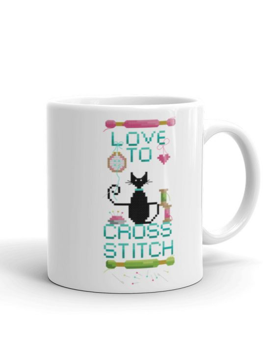 Love to Cross Stitch Coffee Mug featuring a black mini cat sat with all the cross stitch accessories, an embroidery hoop, skeins and spools of thread.