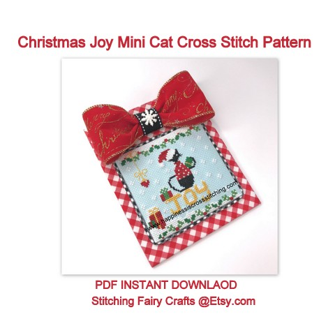 Christmas Mini black cat cross stitch pattern featuring a black cat sat on the word Joy with a Christmas parcel in his tail and snow all around.